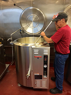 Peter stirs hot fudge in the new 40-gallon market forge kettle